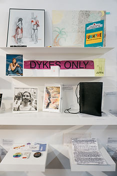 """several submissions on white shelves. Submissions include: drawings, a playboy to fun home, tape that says """"dykes ony,"""" photographs, buttons, letters and a journal"""