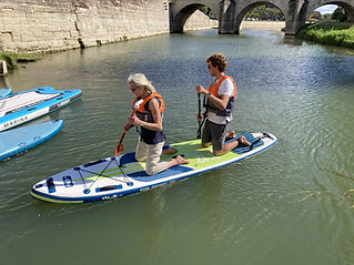 2 people on a paddle board, on their knees, paddling toward a bridge