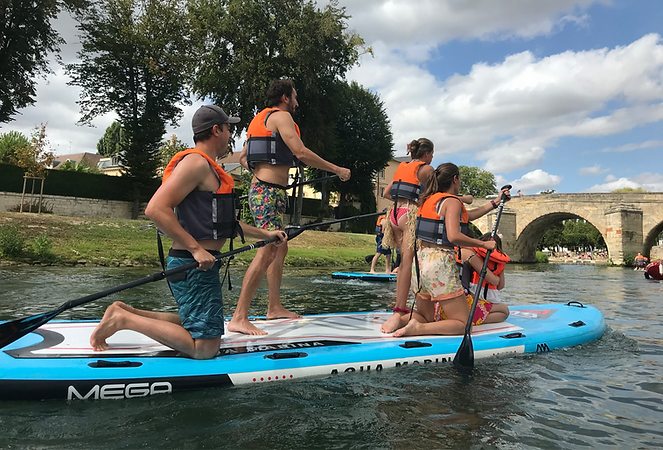 a groupe of 5 people with life jacket and paddle on a paddle board on the river, with a bridge in the background, other people in the background on the river