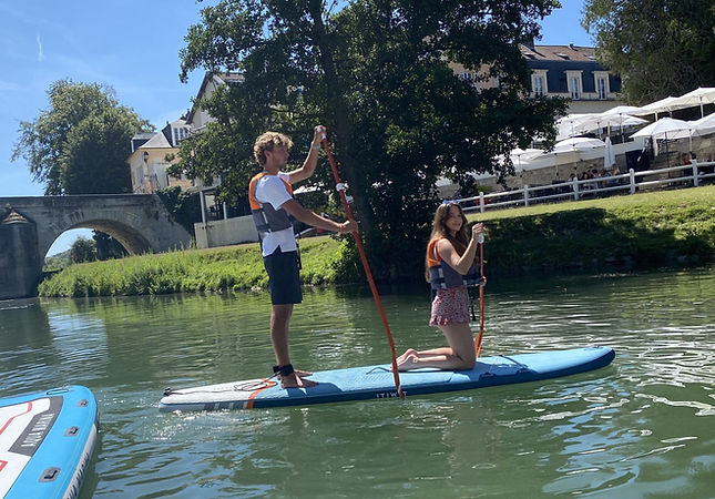 2 people on a paddle board, with life jacket, on a river, one is standing and one is on their knees, behind there is a bridge