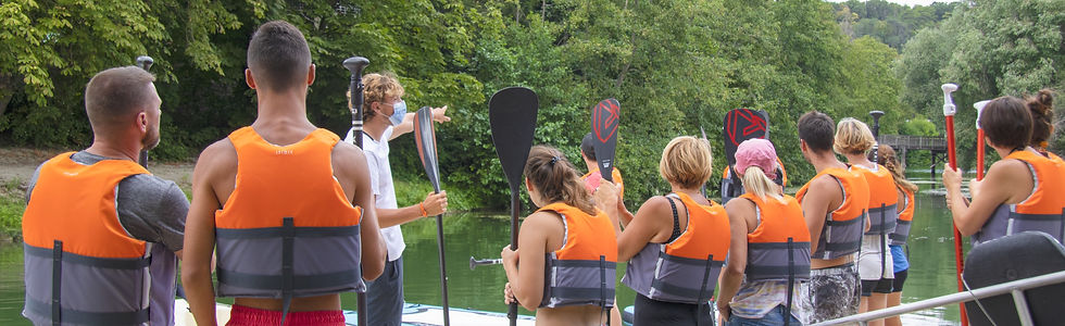 A groupe of people, with paddles and life jackets, in nature, next to a river