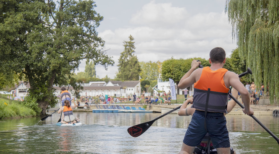 2 groupes of people on paddle boards, wearing life jackets, in the summer, on the river