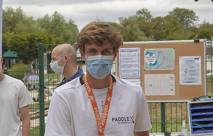 man, wearing a mask on his face, with an orange necklace, other people in the background