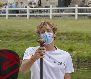 man, wearing a mask on his face, holding a paddle