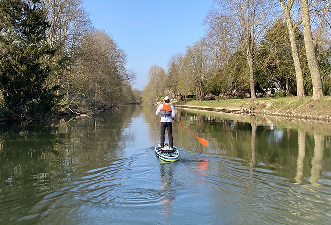 1 person on a paddle board, with a life jacket and a paddle, on a river