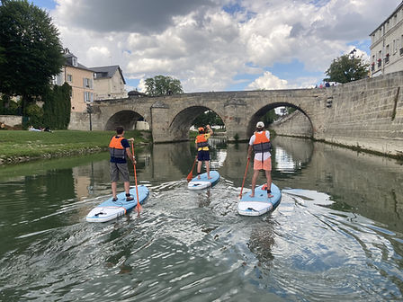 3 people on a stand-up paddle board, wearing life jackets and paddling, on a river, in front of a bridge