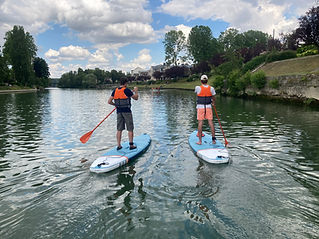 2 people on 2 different paddle boards, standing up, paddling on the river