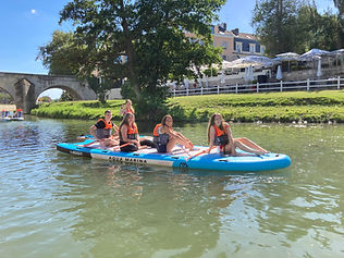 a groupe of 5 people on paddle boards, wearing life jackets, in the summer, on the river