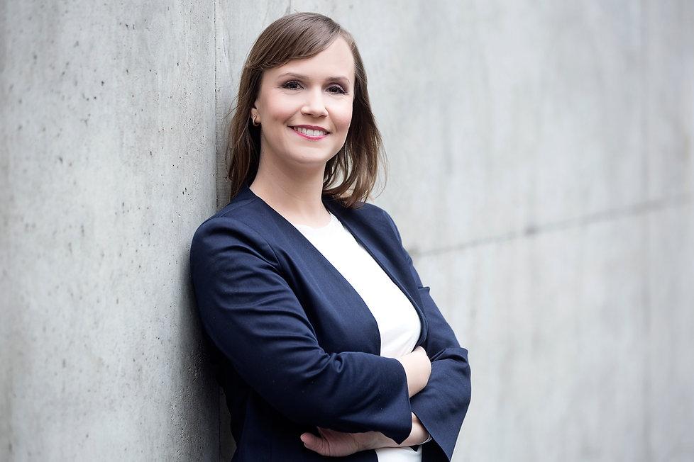 Nina Waldkirch lehnt offen lachend und mit verschränkten Armen an einer Betonwand. Sie trägt einen dunkelblauen Blazer und eine weiße Bluse.