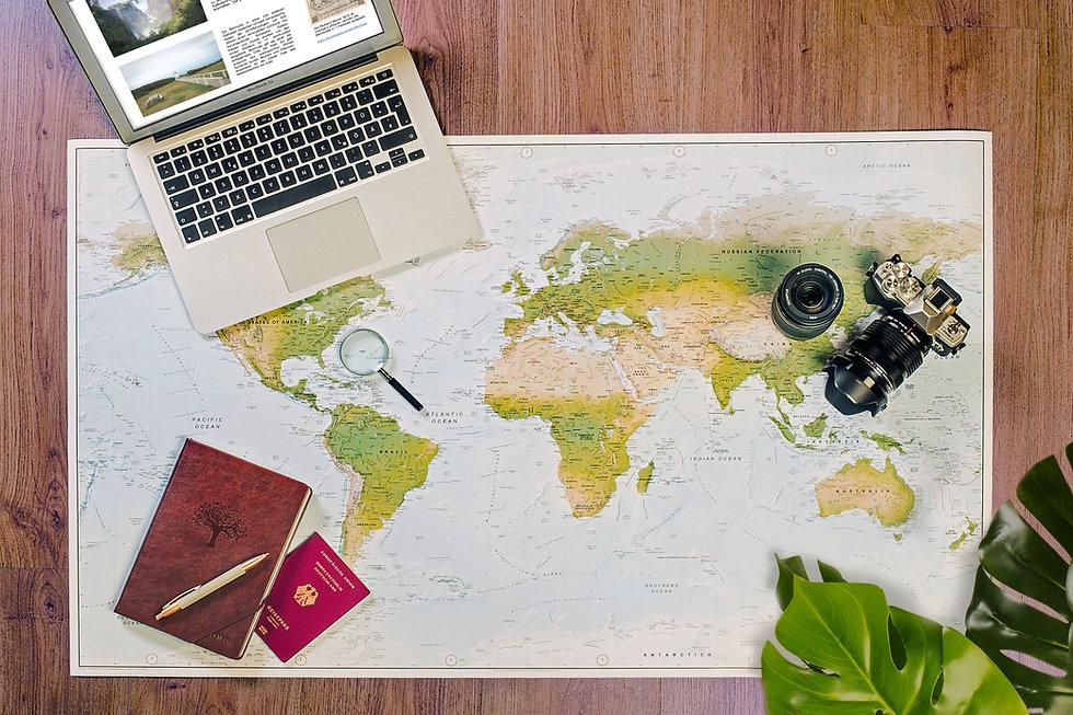 Flat Lay von Weltkarte, Laptop Macbook, Lupe, Fotokamera Olympus mit Objektiv, ledernes Notizbuch, Kugelschreiber, Reisepass und Pflanze auf Holztisch.