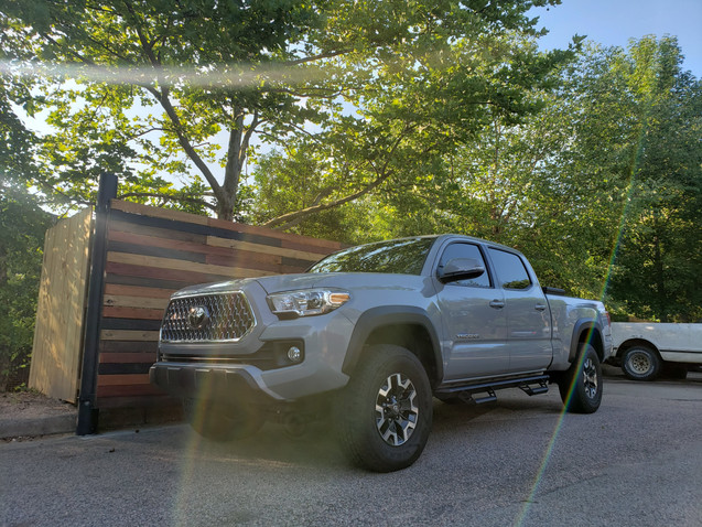 2019 Toyota Tacoma parked next to our modern horizontal slat fence.
