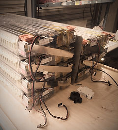 A stack of Tesla modules being tested on the bench, ready to be assemble in to a battery pack.