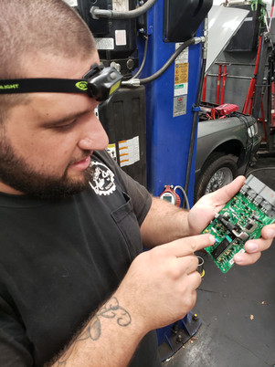 Shop foreman pointing out why an old ABS module had failed internally