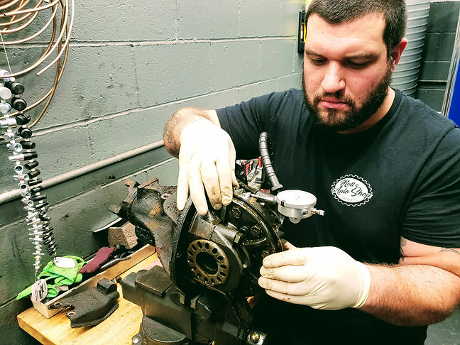 Matt's Auto Shop foreman performing a backlash check on a differential assembly, with a dial indicator, while rebuilding the differential.