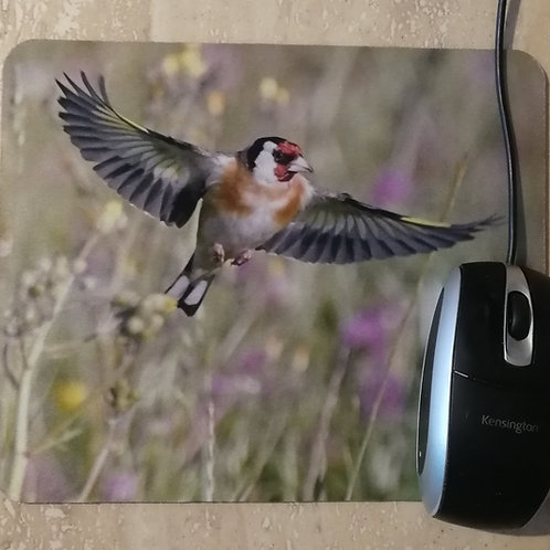 Goldfinch flying through the meadow mousemat