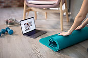 Young sporty slim woman preparing for online fitness training with modern laptop. Healthy