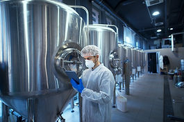 factory-worker-technologist-in-protective-uniform-with-hairnet-and-mask-controlling-food-p