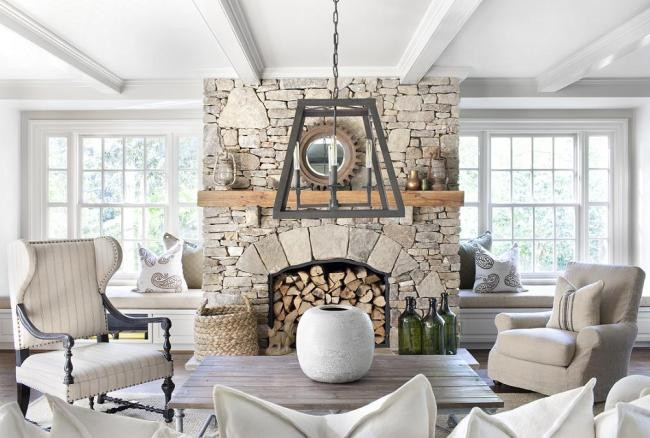 Living room by White Haven Interiors featuring a stone fireplace.