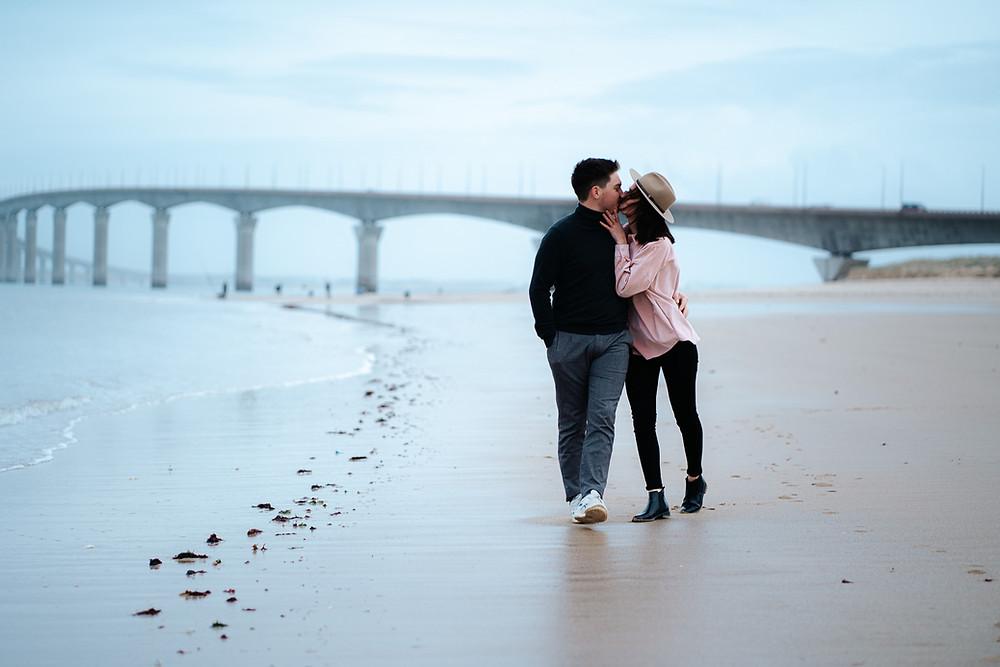 couple s'embrassant sur la plage devant le pont de l'ile de ré
