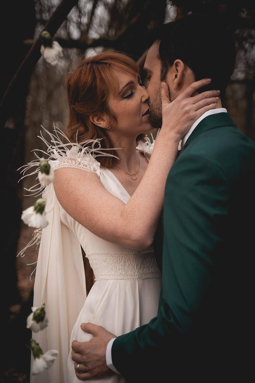 mariés s'embrassent sous l'arche de cérémonie