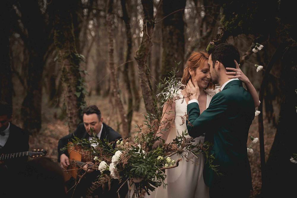 mariés s'embrassent le visage, la mariée tient son bouquet, les musiciens jouent de la guitare