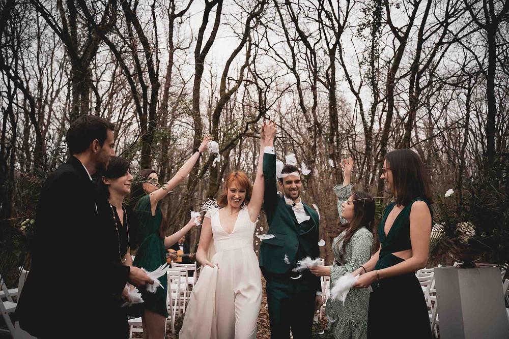 mariés riant, confettis de plumes, bras levés
