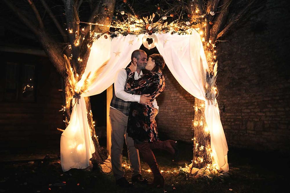 couple qui s'embrasse sous une arche de fleurs illuminée dans la nuit