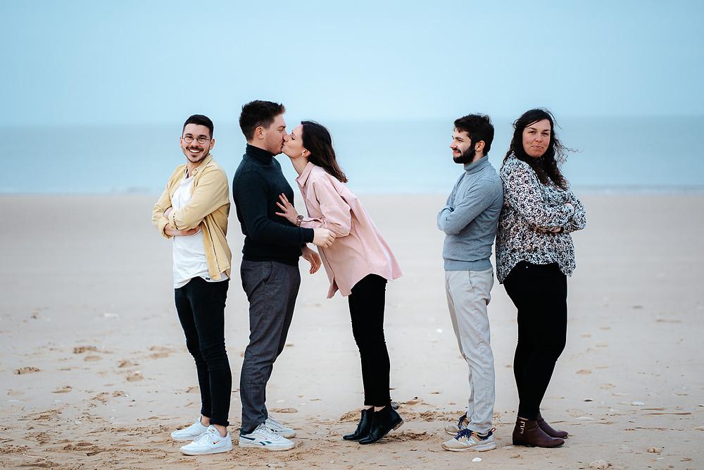 groupe d'amis sur la plage, couple qui s'embrasse
