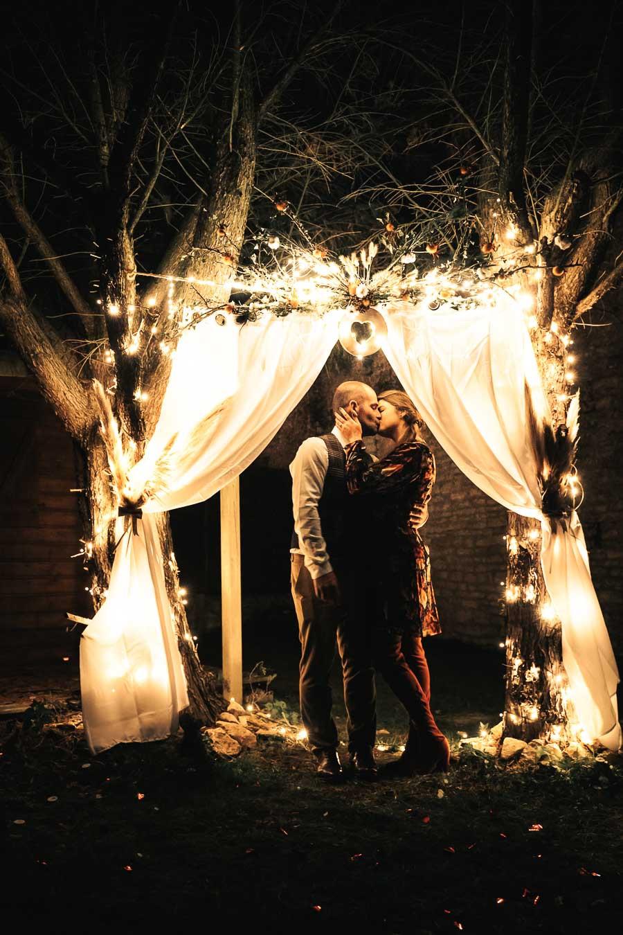 mariés qui s'embrasse sous une arche de mariage illuminée et fleurs séchées