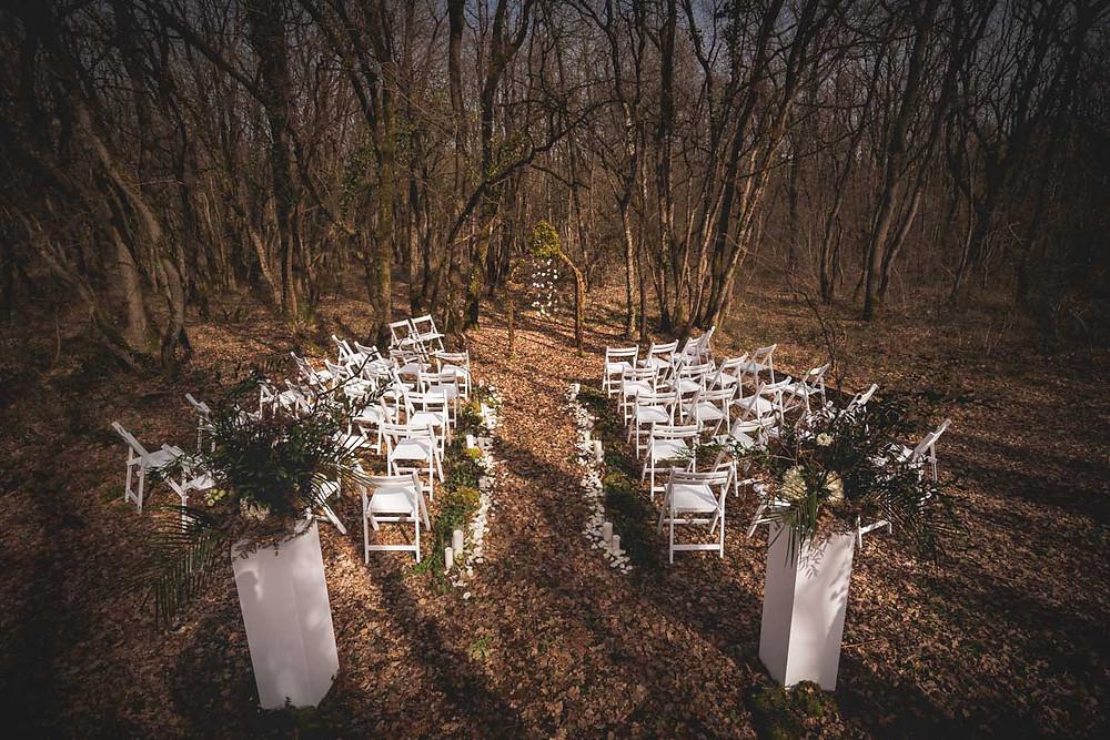 céréomonie laïque en forêt, chaises blanches arc de cercle, compositions florales, arche orininale