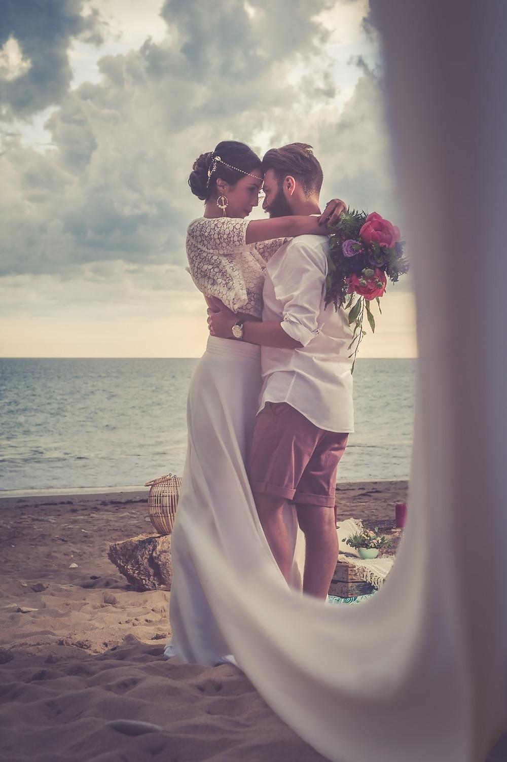 couple sur la plage, bois flotté, robe de mariée blanche, bouquet coloré, hippie chic