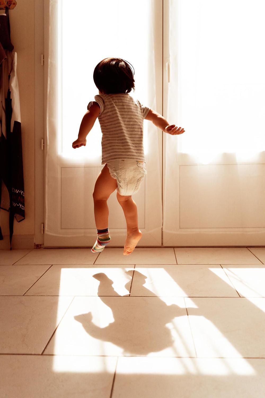 garçon saute devant la fenetre, ombre au sol, contre jour, photographe de famille à la rochelle