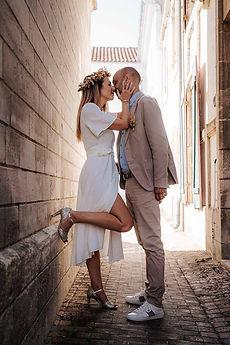 photos de couple, mariés en contre jour, robe courte blanche et couronne de fleurs séchées, la mariée porte des escarpins dorés, le marié porte un costume beige