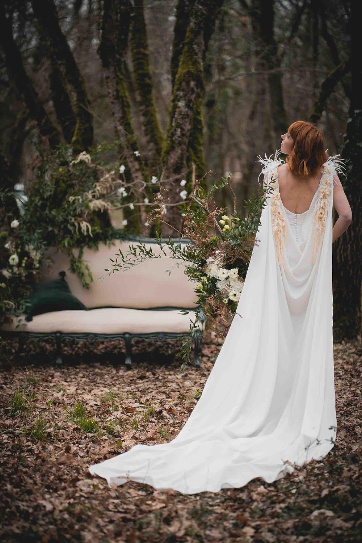 mariée qui se tient debout, vue de dos de sa cape blanche ornée de fleurs séchées