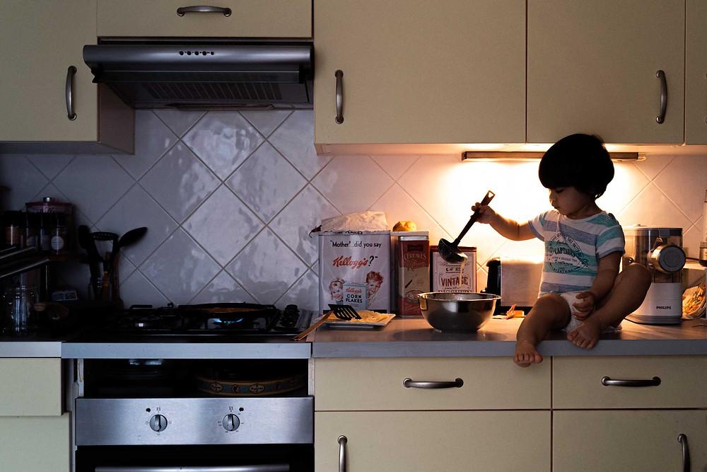 bébé fait des crepes dans la cuisine, photographe de famille à la rochelle