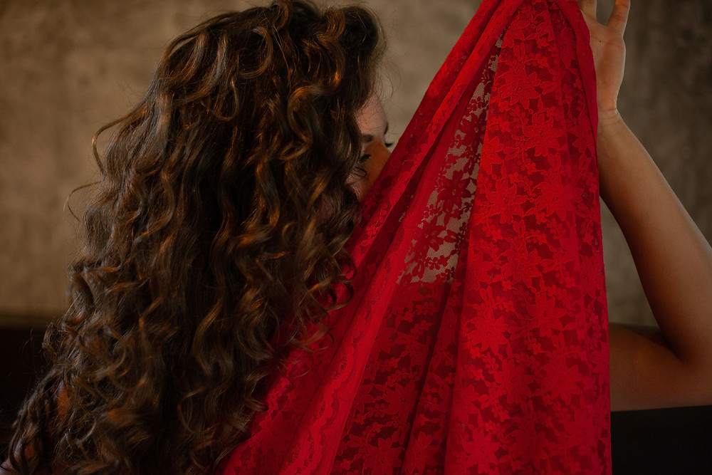 romantic image of beautiful woman holding up a red lace veil
