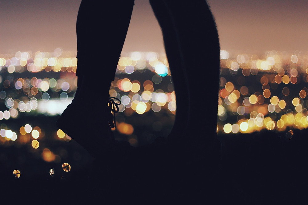 two lovers kissing in front of city lights outline of legs