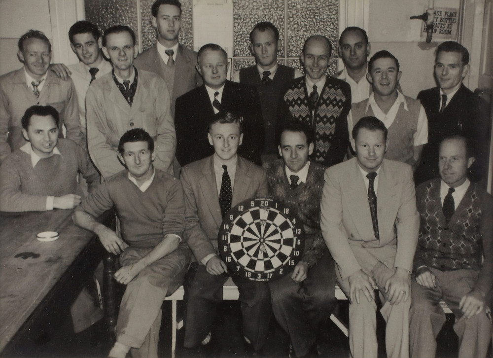 group of white dudes holding a dart board in a black and white picture