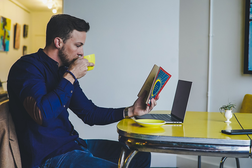man reading a book and drinking coffee in front of laptop