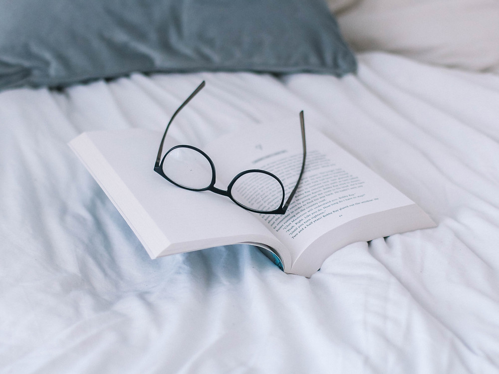 pair of reading glasses sitting on an open book