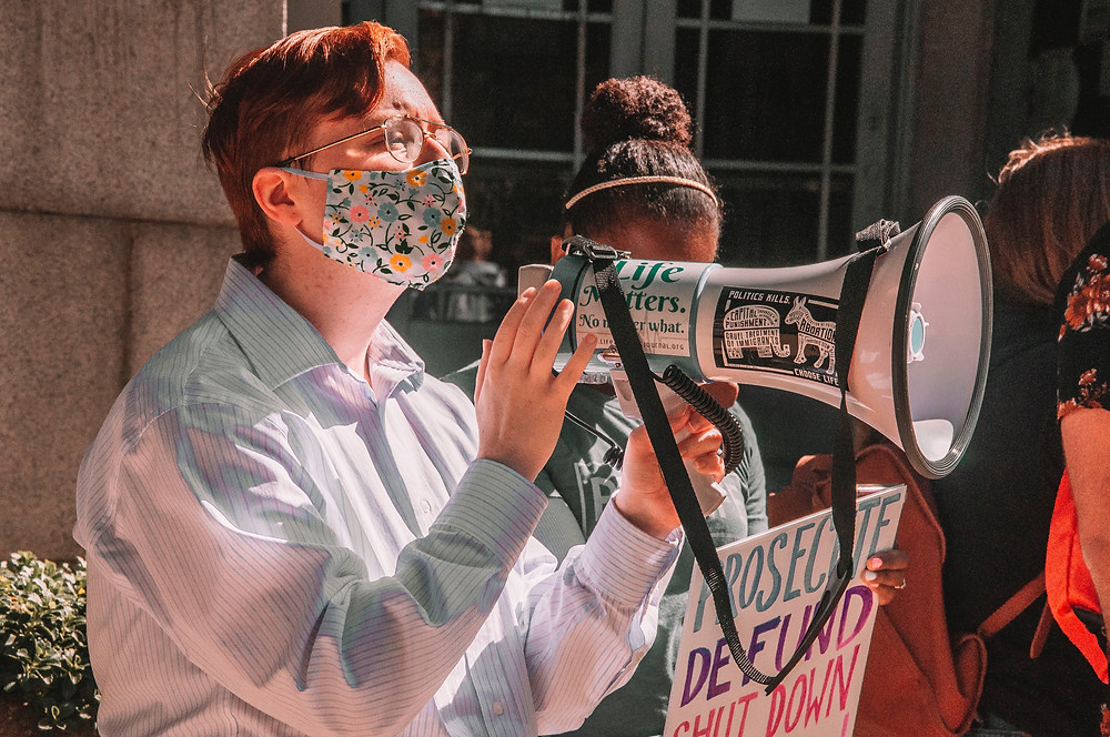 activist standing in mask with large megaphone