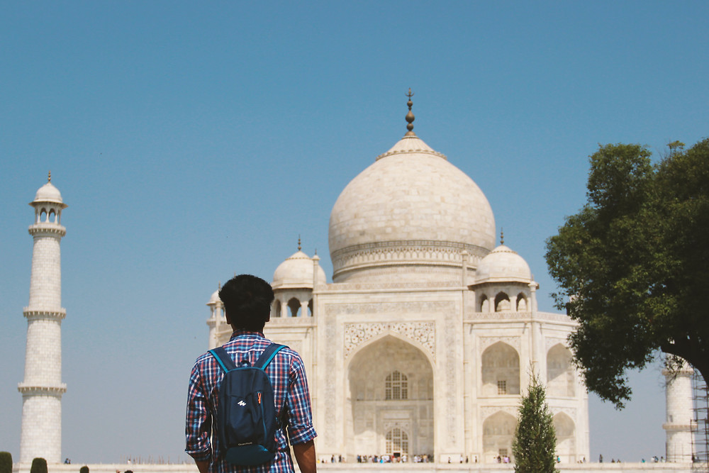 man standing before the Taj Mahal on a sunny day