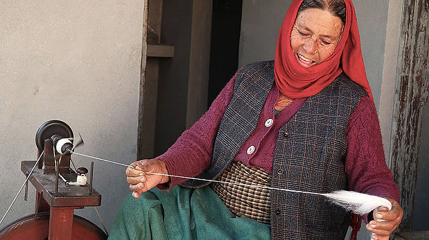 handspinning wool to make handwoven shawls for women