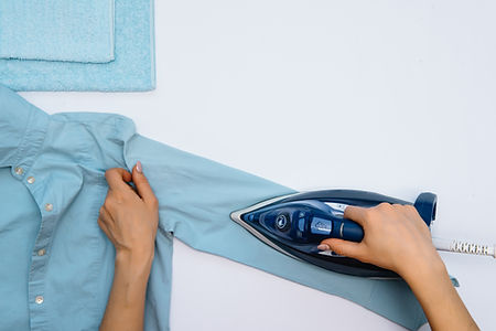 Female hand ironing clothes top view iso