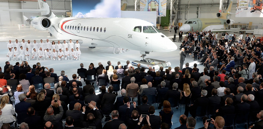 """Dassault unveiled the first Falcon 5X prototype today at its Bordeaux, France factory before an audience of about 500 customers, operators, suppliers and certification authority representatives. The 5,200-nm twinjet is being prepared for its first flight this summer.  Flight-test equipment for the 5X is said to have been improved over previous programs and will, among other benefits, help predict aircraft system reliability. Entry into service was once pegged for mid-2017, but the effects of the Silvercrest engine program delay, announced two weeks ago at the EBACE show, are still under evaluation. Snecma is now planning to have the engine certified in the summer of 2016.  The 5X's cockpit features the first-ever combined vision system, where Elbit merges synthetic and """"real world"""" vision for enhanced situational awareness in poor weather. Sensors can be found in infrared, visible light and """"almost radar"""" wavelengths, according to a Dassault executive.  Cockpit windows are 30-percent larger than on previous Falcons. """"This provides enhanced visibility on visual approaches and allows you to better anticipate the flightpath,"""" chief test pilot Philippe Deleume told AIN.  Its flight control surfaces include flaperons, which combine flaps and ailerons. Senior vice president for civil aircraft Olivier Villa explained this enables the pilot, in a steep approach, to fly the attitude independently from the slope angle. In the cabin, the 8.5-foot (2.58 m) fuselage cross section enables layouts with a full-size bed."""