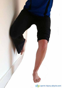 Single leg squat with wall support from the front.