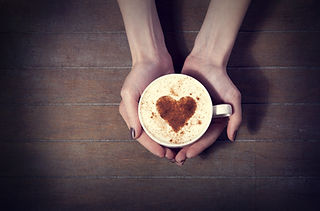 woman holding hot cup of coffee, with he