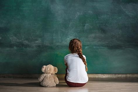 Little autistic girl with teddy bear sit
