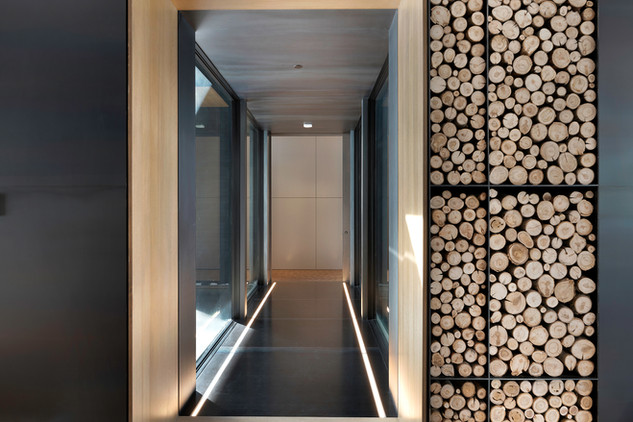 Glass Hallway and firewood feature wall.