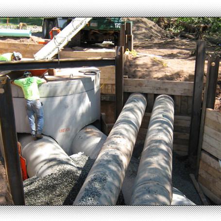 """Instal twin 36"""" concrete storm lines & 10 foot diameter manhole structure."""